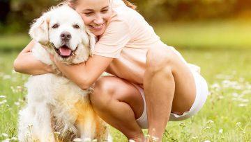 Woman hugs Golden Retriever dog