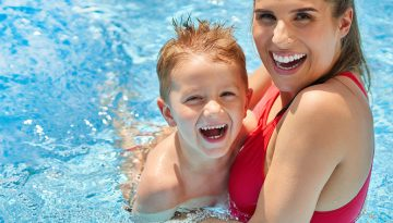Cute boy with his mother playing in swimming pool during summer